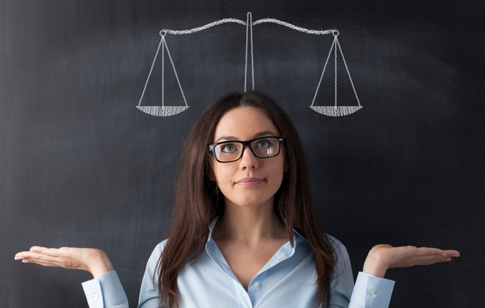 A woman stands with her back against a chalkboard, holding her palms up and looking at a drawing of a balance scale above her head.