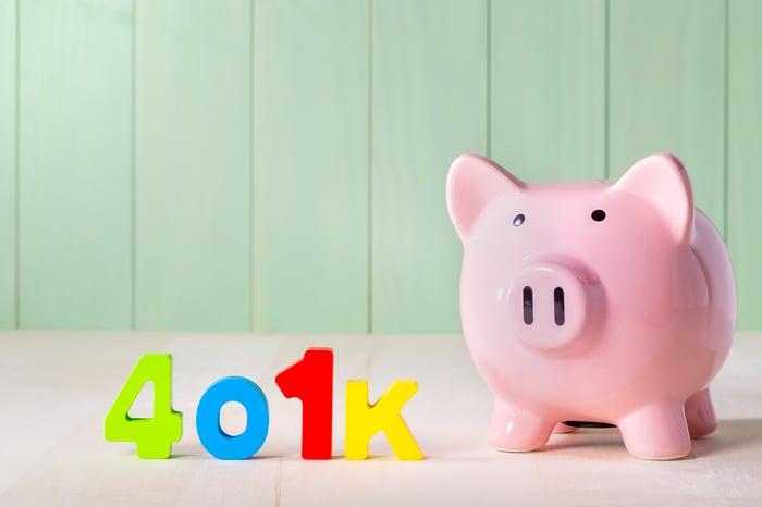The term 401(k) built in blocks standing next to a piggy bank.
