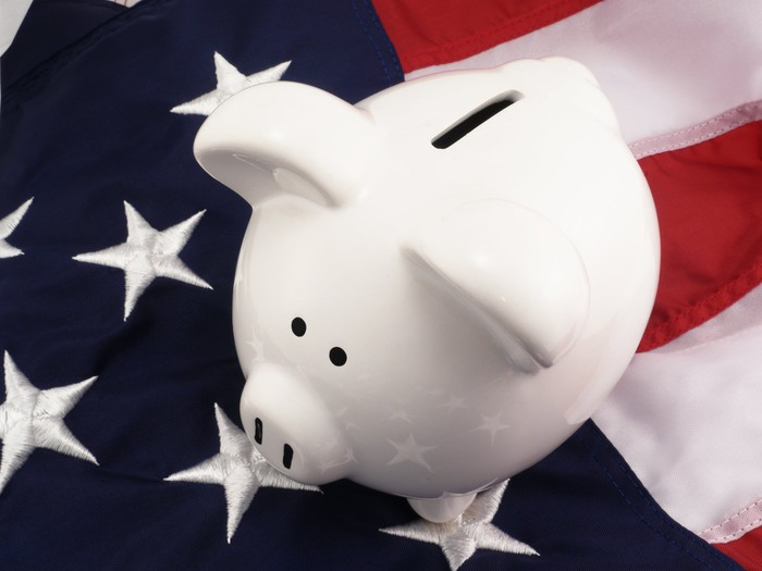 A white piggy bank sits on top of an American flag.