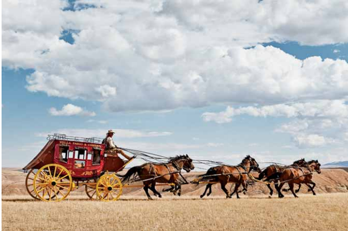 The Wells Fargo state coach traveling over grasslands.