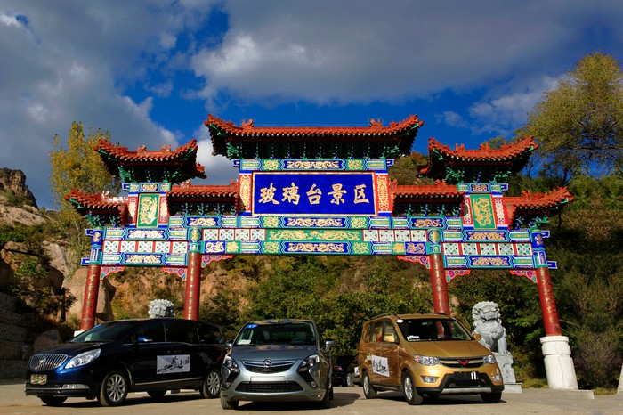 GM vehicles in front of Chinese architecture