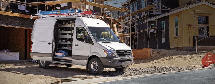 A white Mercedes Benz Sprinter van pulled up at the construction site of a new housing development.