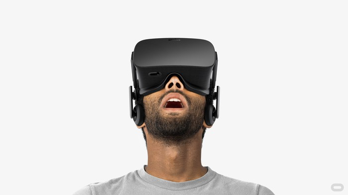 Man with a beard wearing an Oculus headset in a room with a white background.