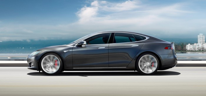 Tesla Model S driving on a coastal road on a partly cloudy day.