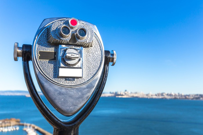 A coin-operated scope looks out on a body of water.