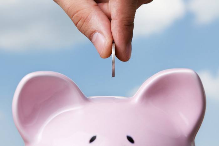 A hand puts a coin in a piggy bank from above.