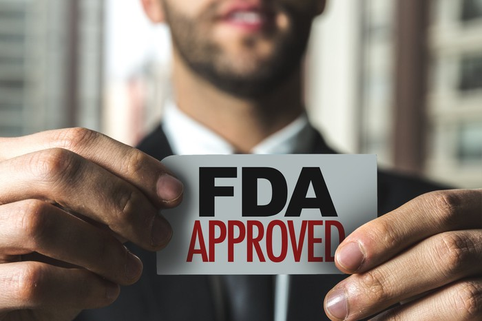 """A man in a suit holding up a card that reads """"FDA Approved."""""""