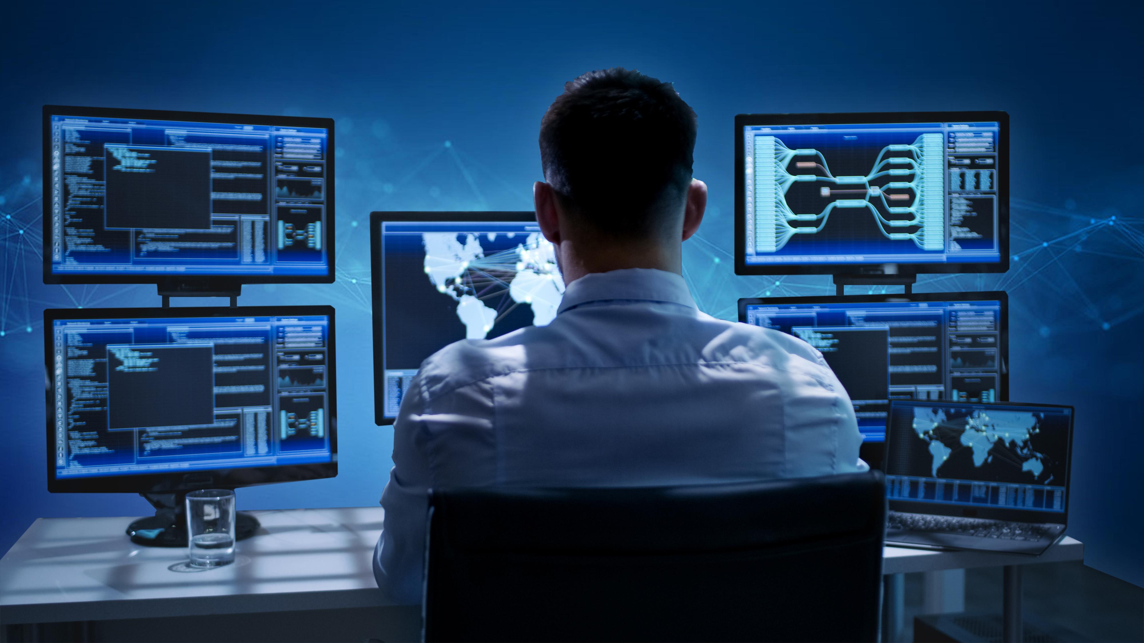 Man looking at several computer screens.