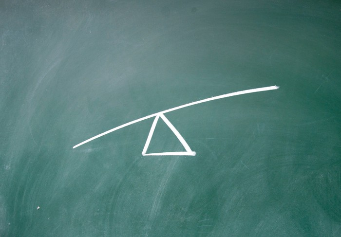 A drawing on a chalkboard of a triangle with a line balanced on top, meant to demonstrate leverage.