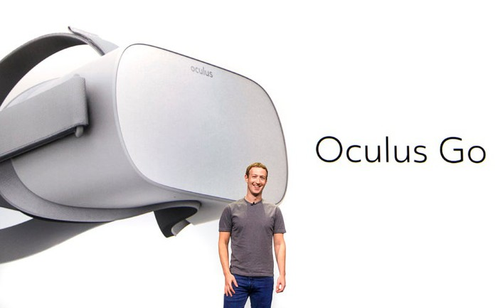 Mark Zuckerberg standing on stage with a picture of Oculus Go behind him