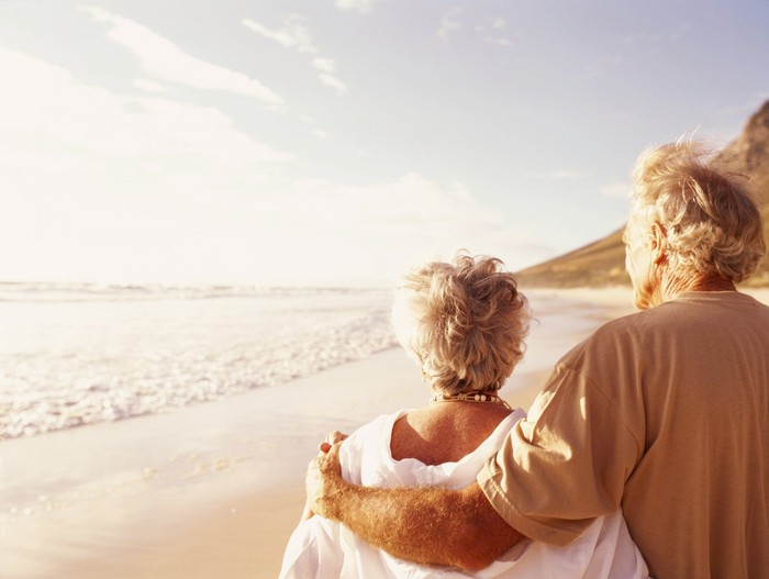 Older couple arm in arm walking on a beach.