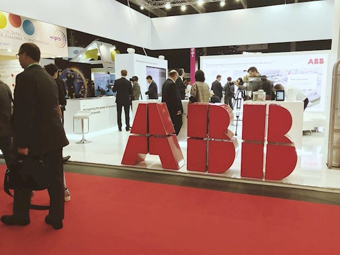 Conference attendees walk past an ABB Ltd booth.
