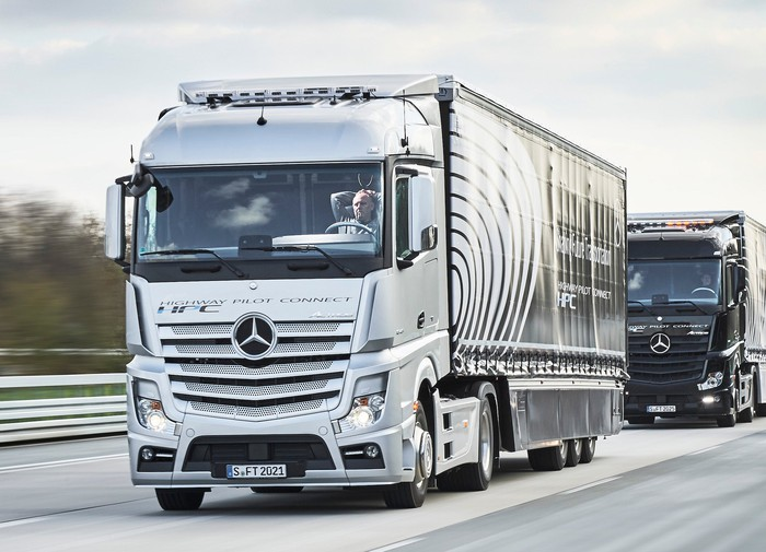 A Mercedes-Benz tractor-trailer truck traveling on a highway. The driver is holding his hands behind his head to show that the vehicle is autonomous.