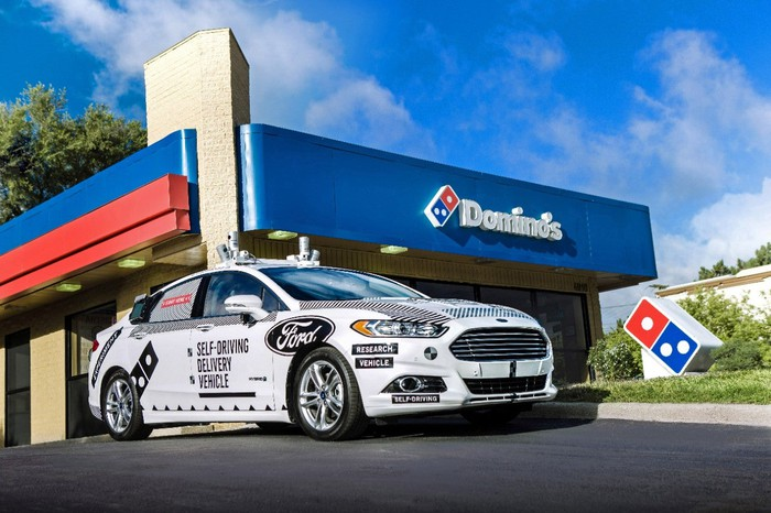 A white Ford Fusion sedan with large logos and visible self-driving hardware parked outside a Domino's pizza restaurant.