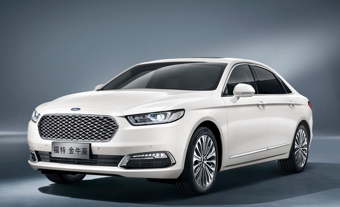 The Ford Taurus as sold in China, a large white four-door sedan with Chinese license plates that shares styling cues with Ford's Fusion and Focus.