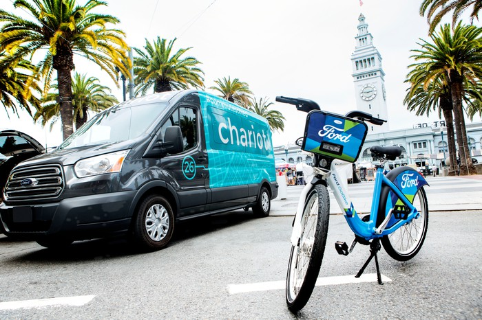 "A Ford Chariot shuttle van and a Ford-branded ""GoBike"" urban bicycle on a city street in San Francisco"