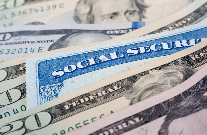 Social Security card in spread-out pile of 20 dollar bills.