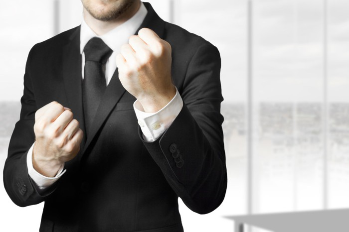 A man in a suit raises clenched fists as if to fight.