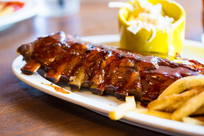 Baby back ribs on white dinner plate with fries