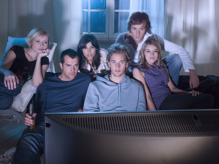 A group of six friends sitting in a darkened living room watching television