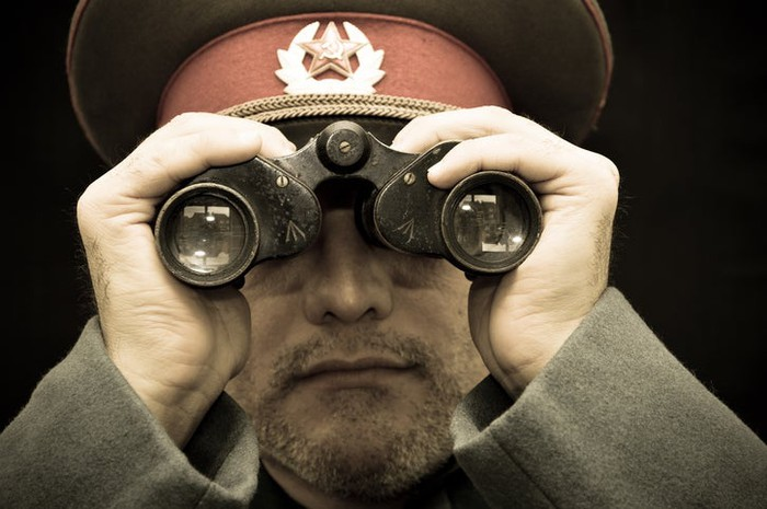 A man in Russian military uniform looking through binoculars