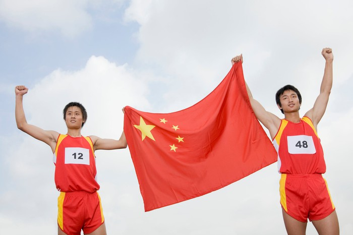 Two athletes holding the Chinese flag between them