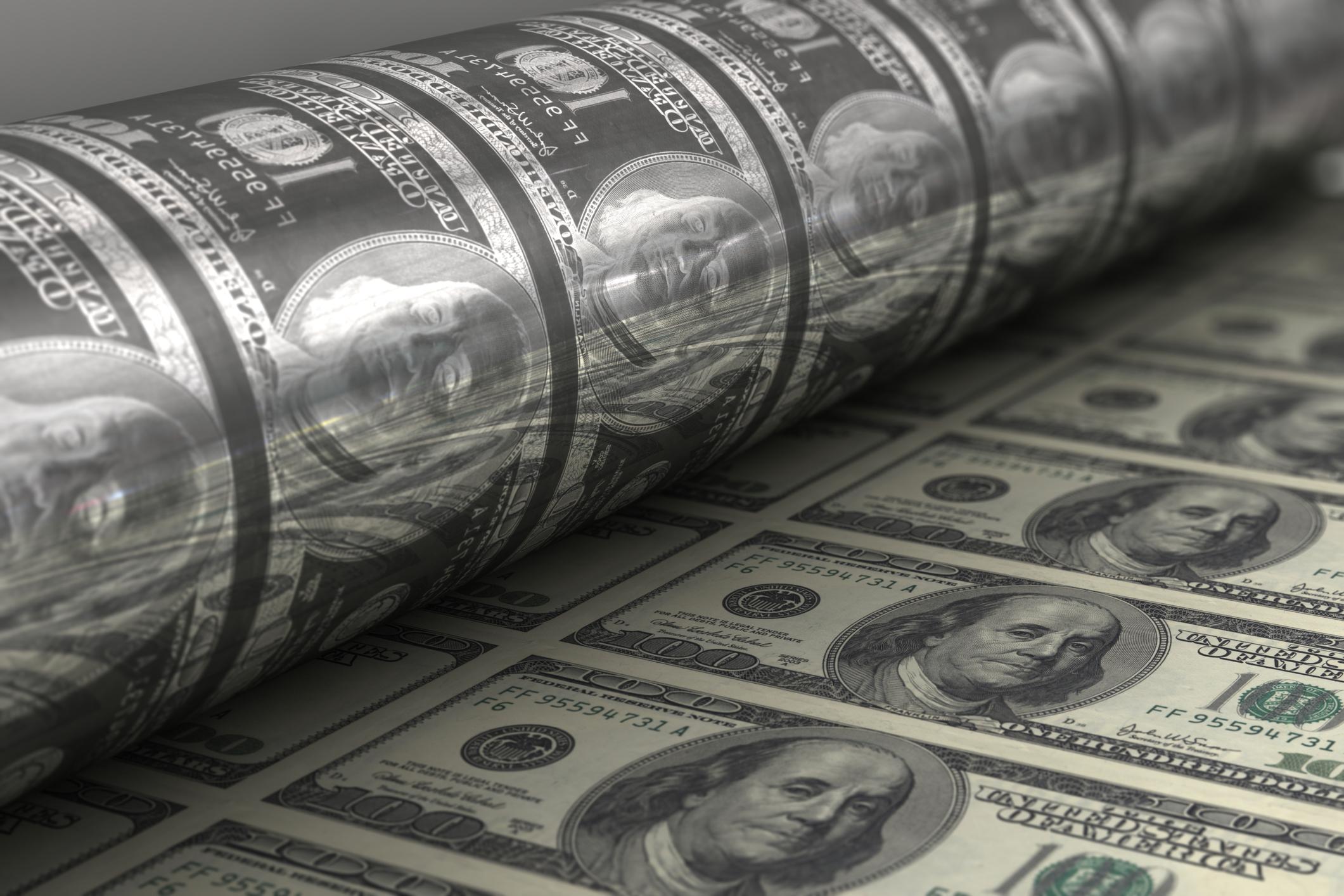 Rolls of $100 bills coming off a printer