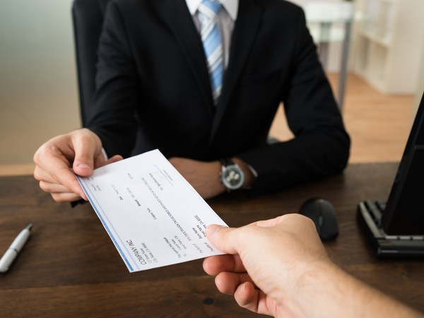 businessman handing check to other person paycheck income earnings wages
