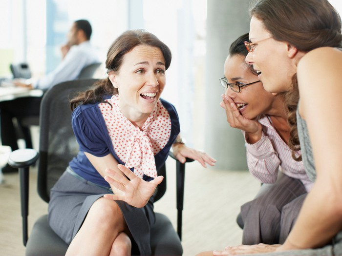 Professionally dressed women chatting in an office setting.