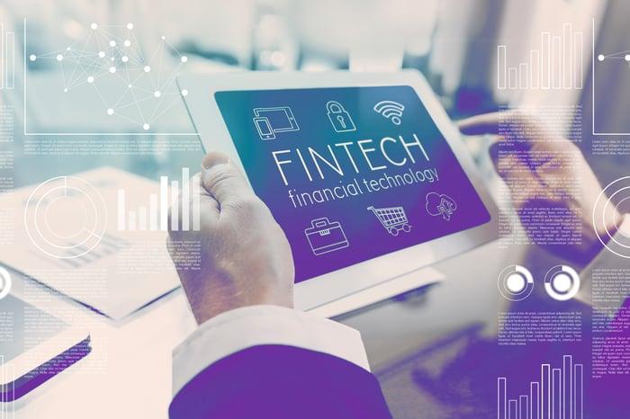 "A man holding a tablet that reads ""FINTECH financial technology""."