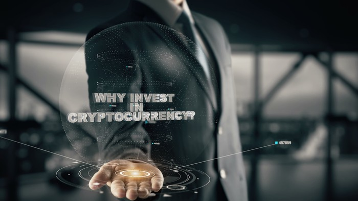"Man in suit holding out hand with computer graphics extending from open hand. Reads ""Why invest in cryptocurrency?"" across the picture."