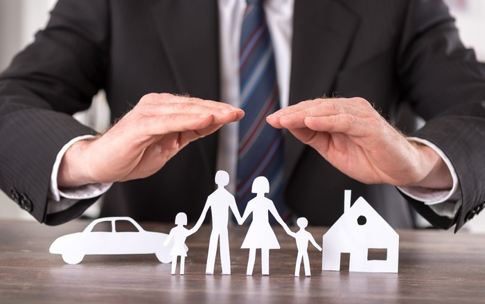 A man in a suit holding his hands over paper cutouts of a family, a car, and a house.