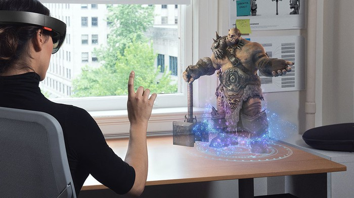 Woman using Microsoft's Hololens to play a game on a tabletop.