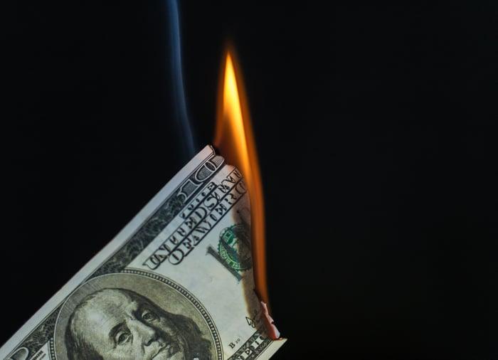 $100 bill burning.