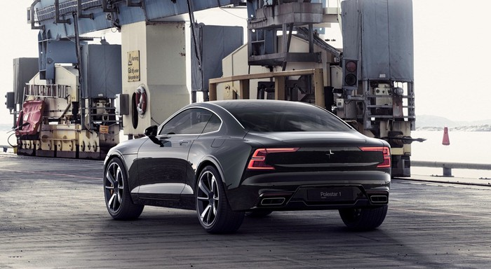 A black Polestar 1 coupe near a waterfront, with industrial equipment in the background.