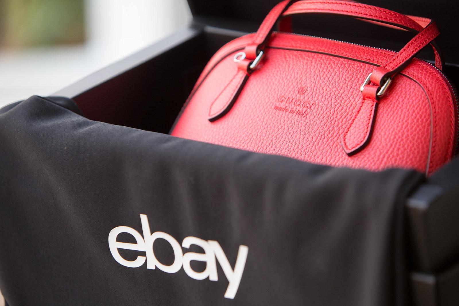 """A handbag sits in a box labelled """"ebay."""""""