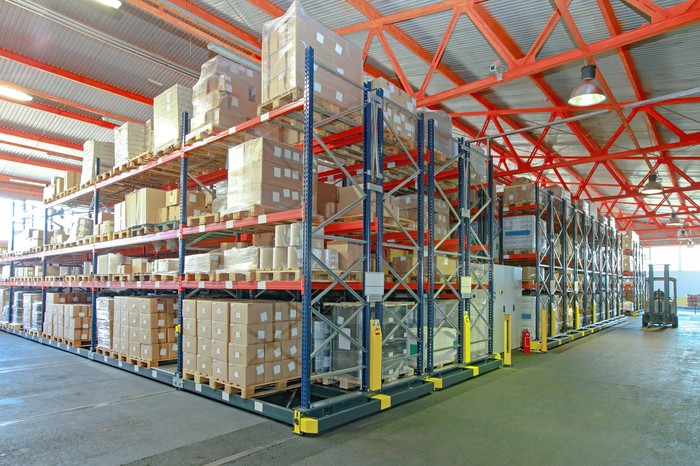 Warehouse with boxes and a forklift picking pallets.
