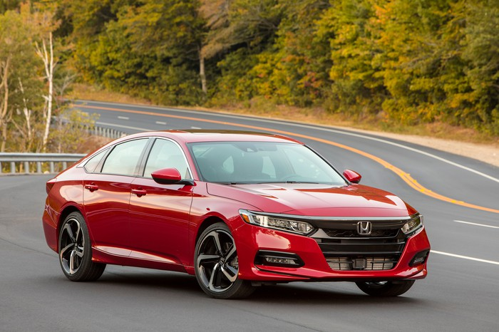 A red 2018 Honda Accord, a midsize sedan with a hatchback-like roofline, on a country road.