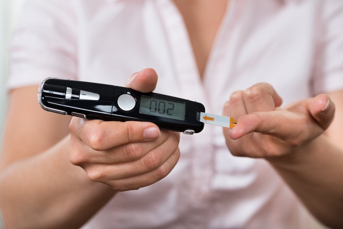 A woman using a glucometer to test her blood sugar level.