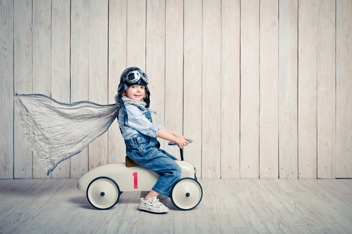 A small boy rides a toy car with a cape on