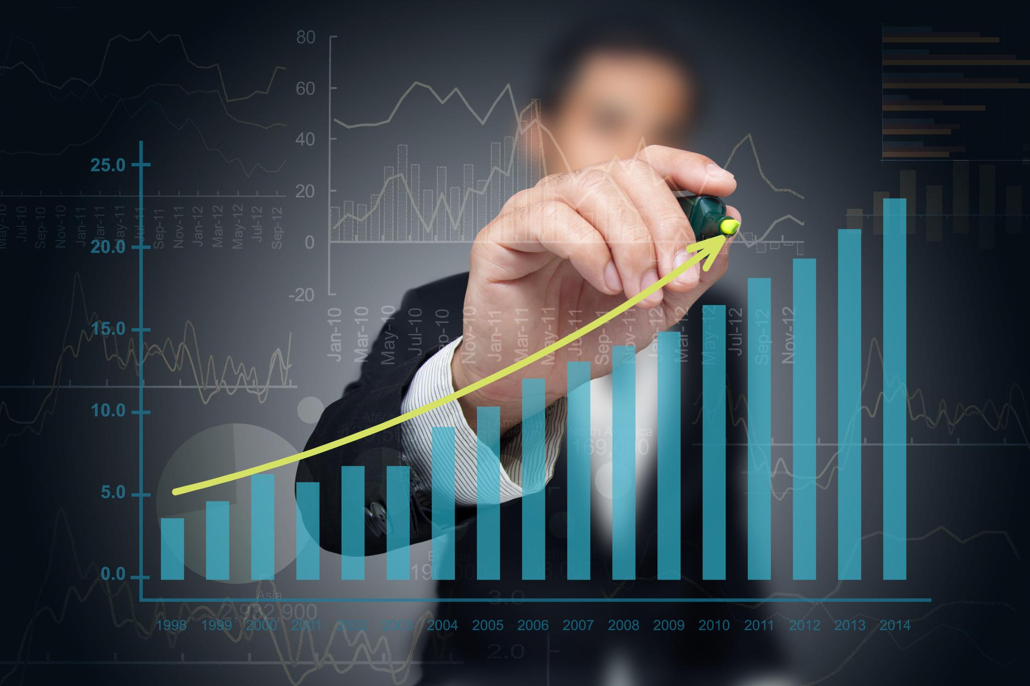 A businessman drawing a line upward above a chart of ascending columns.