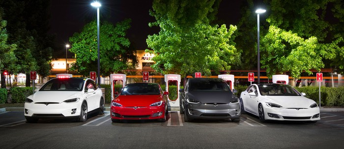 Four Tesla cars charging at a Supercharger station