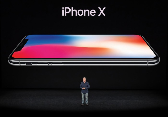 Apple executive Phil Schiller on stage in front of a projected image of the iPhone X.