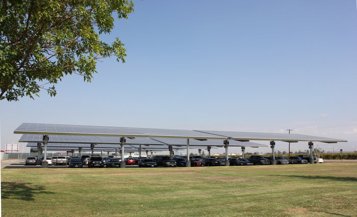Solar carport with cars under it on a sunny day.