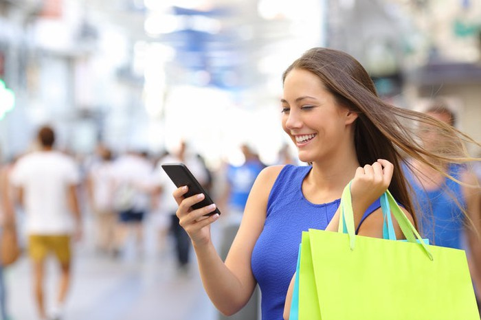 Smiling woman with shopping bags standing in street, looking at mobile device.