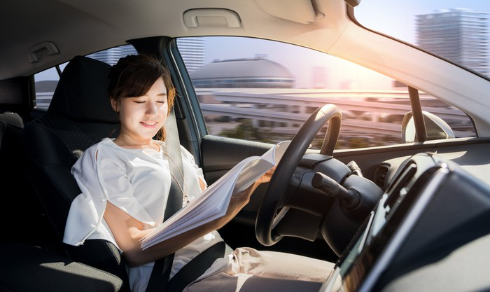 Woman reading magazine in driverless vehicle