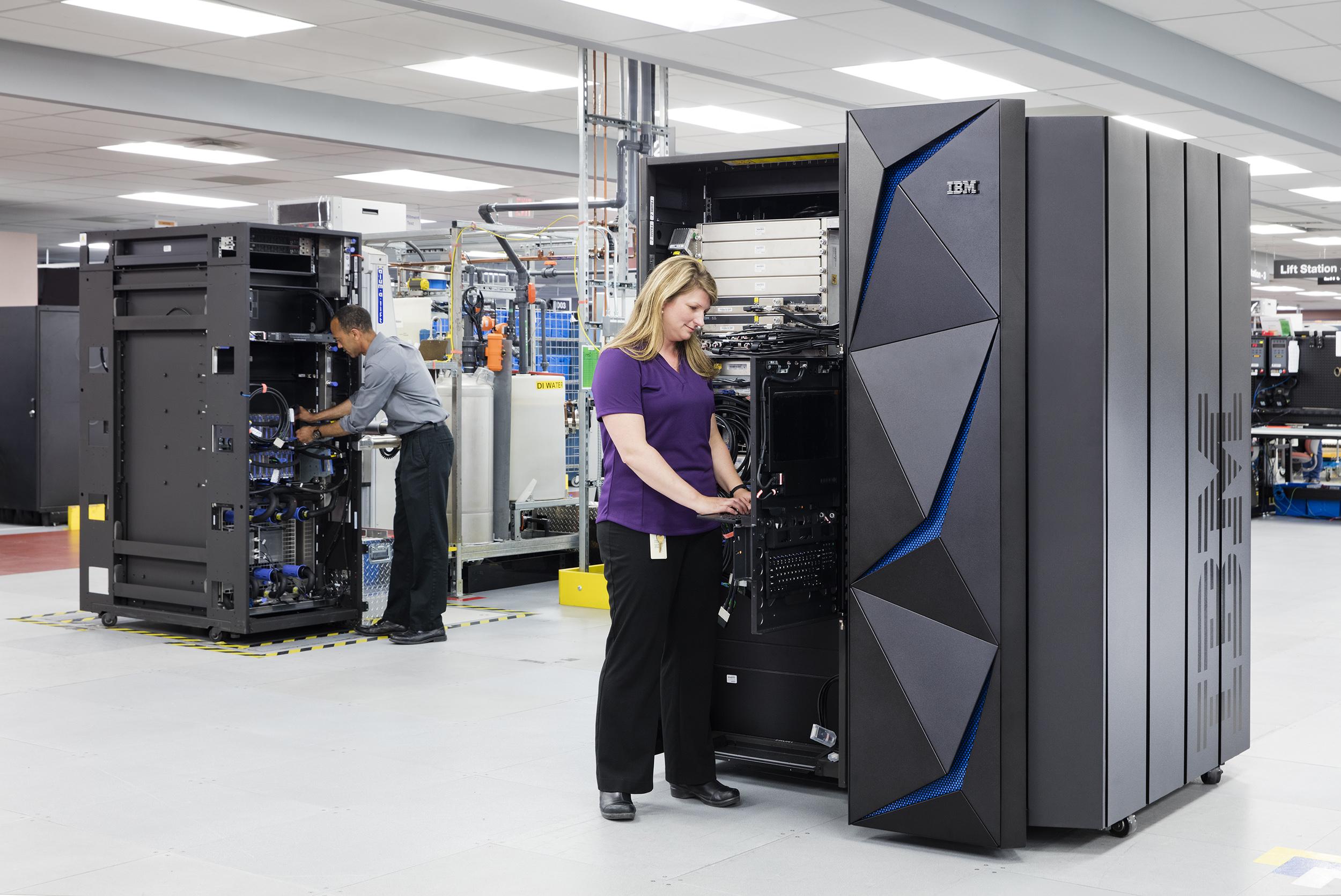 Tech staffers installing new IBM mainframes in a data center.