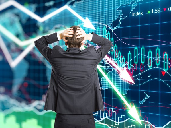 Man holding head as stock chart falls