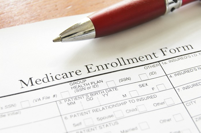 Medicare enrollment form with red pen lying on top of the sheet.