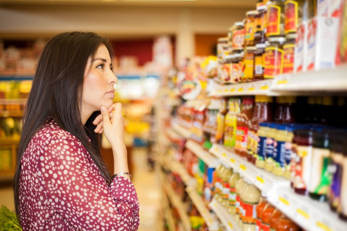 Woman standing in an aisle at a grocery store trying to decide what to buy.